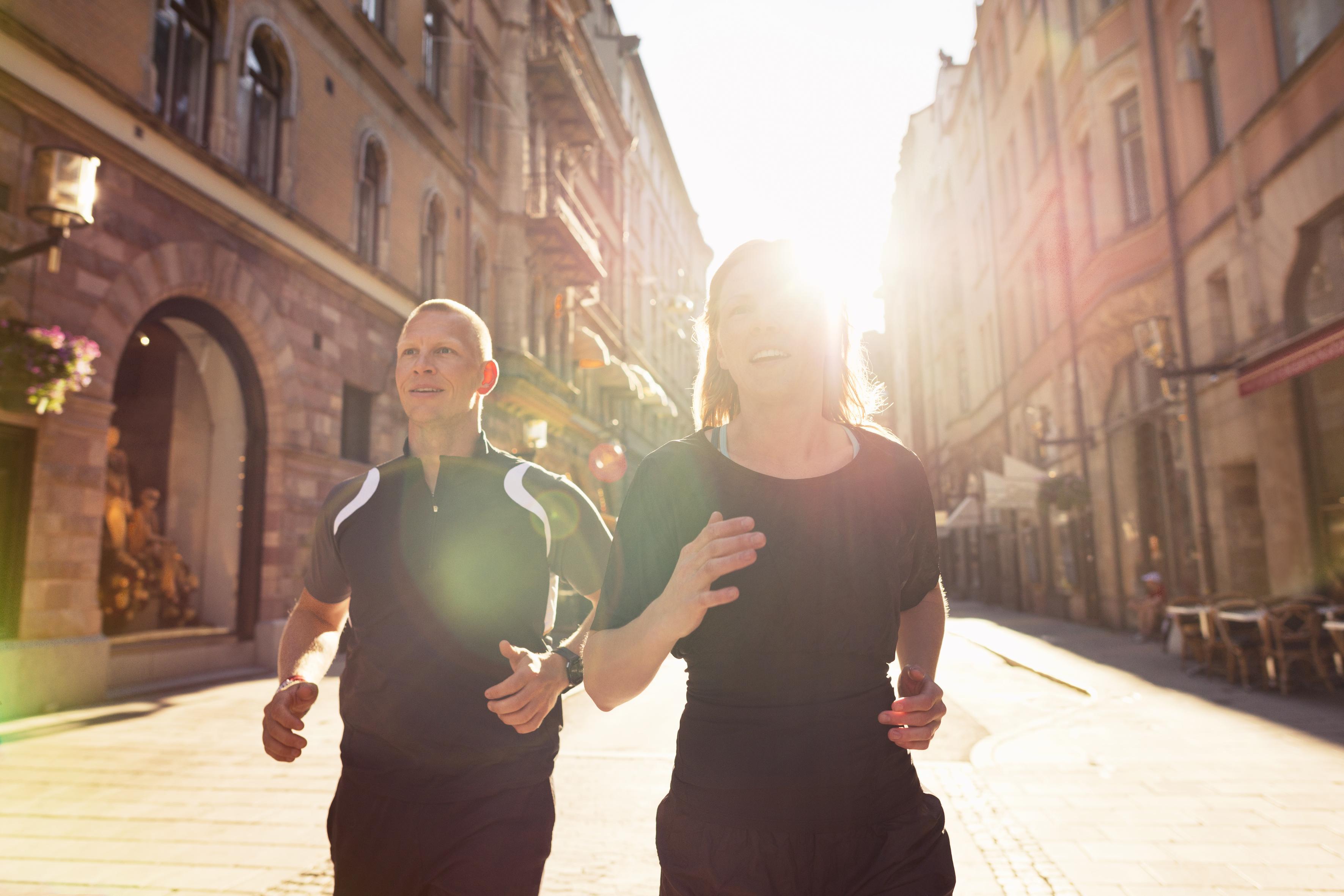 nainen ja mies kadulla. Aurinko paistaa taustalla.